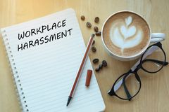 Workplace harassment concept on notebook with glasses, pencil an. D coffee cup on wooden table. Business concept stock photography
