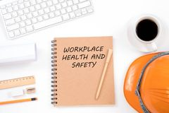 Workplace health and safety concept. Top viwe of modern workplace with safety helmet, office supplies, a cup of coffee and. Keyboard on white background stock photos