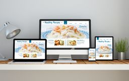 Workplace with healthy recipes online responsive website on devi. A computer, laptop, smartphone and tablet on a desktop workspace with healthy recipes Stock Image