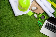 Workplace with helmet, blueprints, laptop and notepad on grass b. Ackground. Top view with copy space Stock Photos