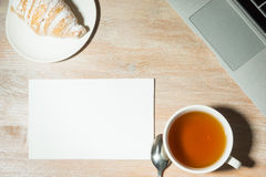 Workplace at home with laptop, tea and croissant. Top view . Stock Photo
