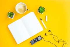 Workplace of the journalist on a bright yellow background. Workplace of the journalist with a dictaphone, headphones, a notebook, a pen and green plants on a Royalty Free Stock Photos