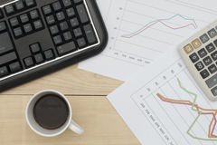 Workplace with keyboard, graph, calculator, and coffee on wood table Royalty Free Stock Photos