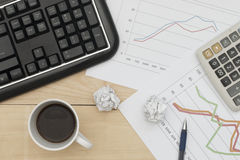 Workplace with keyboard, graph, calculator, pan, and coffee. Royalty Free Stock Image
