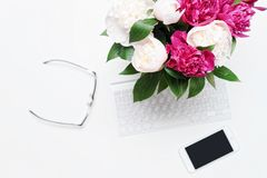 Workplace keyboard mobile phone pink peony flowers glasses. Workplace with keyboard, notebook, glasses, mobile phone and pink and white peony flowers on the royalty free stock image