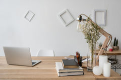 Workplace with laptop, books, candles and office supplies Royalty Free Stock Photos