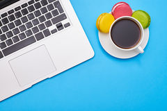 Workplace with a laptop and coffee over blue flatlay. Cropped shot of a workplace with a laptop and coffee with tasty macaroons over blue flatlay. Place for copy Stock Photos