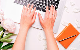 Workplace with laptop female hands notebook pen and peony flowers Royalty Free Stock Images