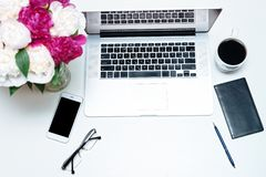 Workplace with laptop, notebook, mobile phone, glasses, pen and pink and white peony flowers on the white table background. Flat royalty free stock images