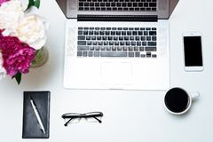 Workplace with laptop, notebook, mobile phone, pen and pink and white peony flowers and glasses on the white table background. Flat lay, top view stock photos