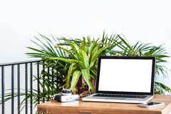 Workplace with laptop on table at home. Laptop in a coffee shop at office desk, typing on computer sitting at wooden Background royalty free stock image