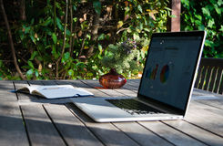 Workplace with laptop on the terrace, notebook with analytical graphs and pot of flowers Stock Photos