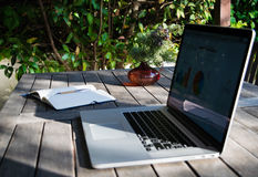 Workplace with laptop on the terrace, notebook with analytical graphs and pot of flowers Royalty Free Stock Images
