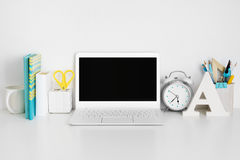 Workplace with laptop on white table, business or education concept.  Royalty Free Stock Photography