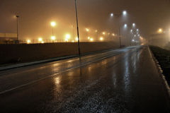Workplace. Misty road with lights that shine in fog Stock Image
