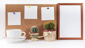 Workplace Mockup. Banner. Three white stickers, empty vertical frame, white cup, two cactus on a white background royalty free stock image