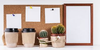 Workplace Mockup. Scandinavian style banner. Three white stickers, empty vertical frame, two cups of coffee, two cactus on a white. Background stock images