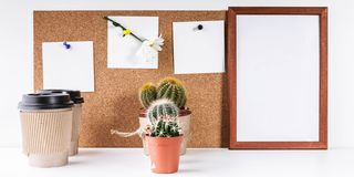 Workplace Mockup. Scandinavian style banner. Three white stickers, empty vertical frame, two cups of coffee, two cactus on a white. Background royalty free stock image