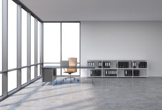A workplace in a modern corner panoramic office with copy space in the windows. A black desk with a laptop, brown leather chair an Royalty Free Stock Photo