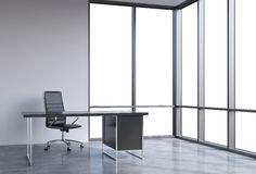 A workplace in a modern corner panoramic office, copy space on windows. A black leather chair and a black table. A concept of financial consulting services. 3D Stock Photos