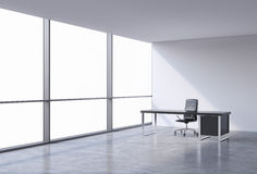 A workplace in a modern corner panoramic office, copy space on windows. A black leather chair and a black table. A concept of fina Stock Photography