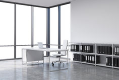 A workplace in a modern corner panoramic office with copy space in the windows. A white desk with a laptop, white leather chair an. D a bookshelf with black Stock Photo