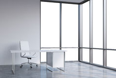 A workplace in a modern corner panoramic office, copy space on windows. A white leather chair and a white table. A concept of fina Royalty Free Stock Photography