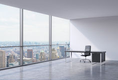 A workplace in a modern corner panoramic office in New York, Manhattan. A black leather chair and a black table. Stock Photography