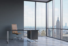 A workplace in a modern corner panoramic office in New York, Manhattan. A brown leather chair and a black table. Royalty Free Stock Photos