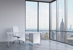 A workplace in a modern corner panoramic office in New York, Manhattan. A white leather chair and a white table. Stock Photography