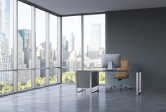 A workplace in a modern corner panoramic office with New York view.. A black desk with a modern computer and brown leather chair. A concept of consulting Stock Images