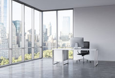 A workplace in a modern corner panoramic office with New York view.. A white desk with a modern computer, black leather chair. A concept of consulting services Stock Photos