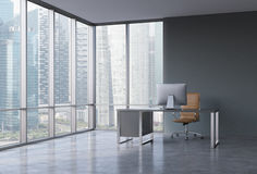 A workplace in a modern corner panoramic office with Singapore view. A black desk with a modern computer and brown leather chair. Stock Image
