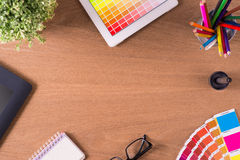 Workplace. Modern office workplace with digital tablet, notepad, colorful pencils, cup of coffee, and color swatches on a desktop. View from the top royalty free stock photo