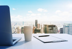 A workplace in a modern panoramic office in Manhattan, New York City. A laptop, notepad and a coffee cup are on the white table. 3 Royalty Free Stock Image