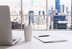 A workplace in a modern panoramic office in Manhattan, New York City. A laptop, notepad and a coffee cup are on the white table. 3 Stock Photos