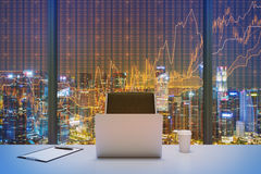 A workplace in a modern panoramic office with New York evening view and financial chart over the window. Laptop, writing pad and a cap of coffee are on the royalty free stock image