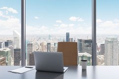 A workplace in a modern panoramic office with New York view. A grey table, brown leather chair. Stock Photos