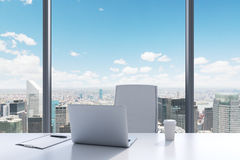 A workplace in a modern panoramic office with New York view. A white table, white leather chair. Royalty Free Stock Photo