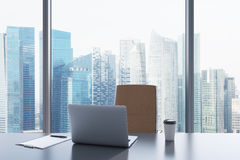 A workplace in a modern panoramic office with Singapore view. A grey table, brown leather chair. Laptop, writing pad for notes and a cap of coffee are on the Royalty Free Stock Image
