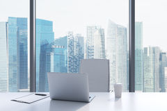 A workplace in a modern panoramic office with Singapore view. A white table, white leather chair. Stock Photo