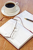 Workplace at morning. Coffee, notebook, pens, glasses on the table Royalty Free Stock Photos