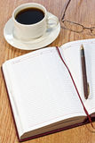 Workplace at morning. Coffee, notebook, pens, glasses on the table Stock Images