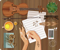 Workplace Music concept. Top view with textured table, feather, violin, bow, music paper Royalty Free Stock Images