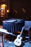 Workplace of musicians on stage. High chair, guitar and other musical instruments. Stand with notes in the foreground royalty free stock photography