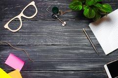 workplace na widok desktops telefon, notatnik, pióro, szkła, klucze na czarnym drewnianym tle Biznes zdjęcie royalty free