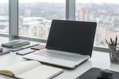 Workplace with notebook laptop Comfortable work table in office windows and city view. Stock Image