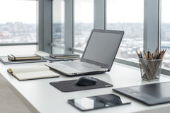 Workplace with notebook laptop Comfortable work table in office windows and city view. Stock Photos