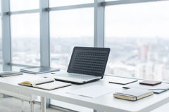 Workplace with notebook laptop Comfortable work table in office windows and city view. Stock Images
