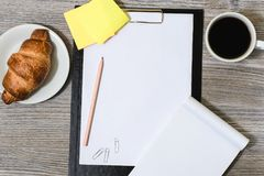Workplace of office accessorise: clipboard, cup of coffee, tasty. Croissant, notebook and stickers Stock Photo